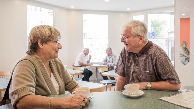 Zwei ältere Leute sitzen an einer Theke und reden miteinander