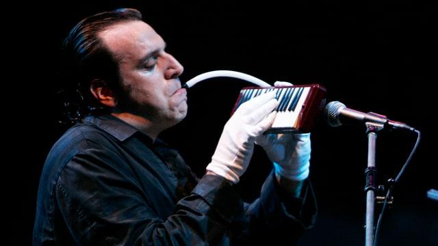 Ein Mann in schwarzem Morgenrock spielt mit weissen Handschhen auf einem Mini-Klavier, das er in der anderren Hand hält. Davor ein Mikrophon.