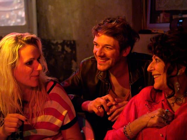 Drei Menschen unterhalten sich: Eine Frau mit blonden Haaren, ein junger Mann und eine Frau.