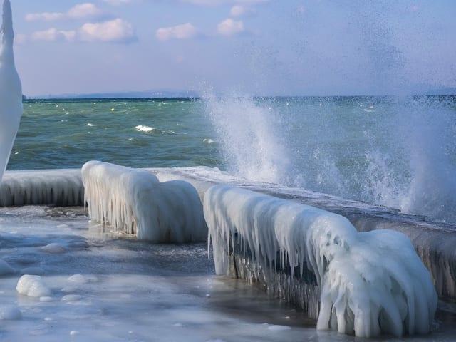 Uferpromenade mit Sitzbank, die von Eis überzogen ist. Auf dem Wasser mit Bise Wellen.
