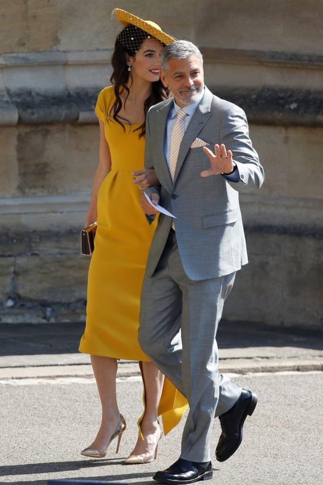 Amal Clooney im gelben Kleid und George Clooney im hellgrauen Anzug