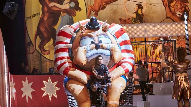 Eine Frau fährt auf der Theaterbühne ein Fahrrad, auf dem ein aufgeblasenes Monster montiert ist.