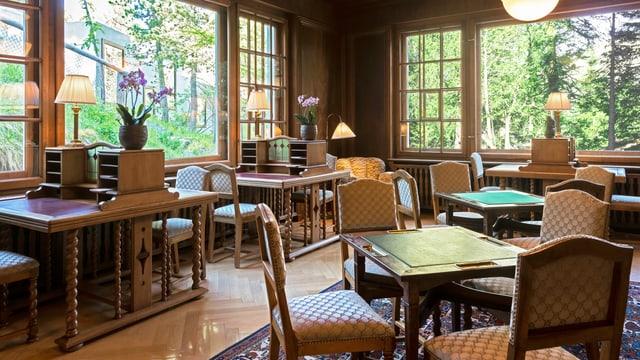 Ein edles Zimmer mit Tischen und Stühlen.