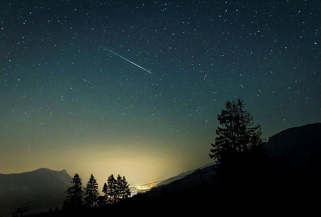 In den Flumser Bergen in der Nacht mit sternenklaren Himmel und einer Sternschnuppe.