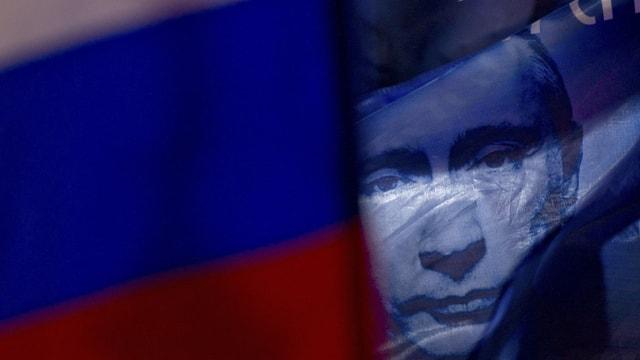 Putin-Bild hinter einer Russland-Flagge