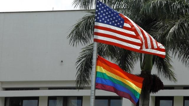 US- und Regenbogenfahne an einem Mast.