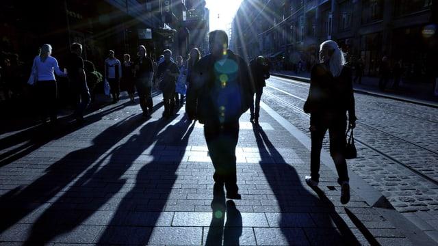Menschen gehen im Gegenlicht ein Trottoir in Helsinki entlang, rechts ein Tramgleis.