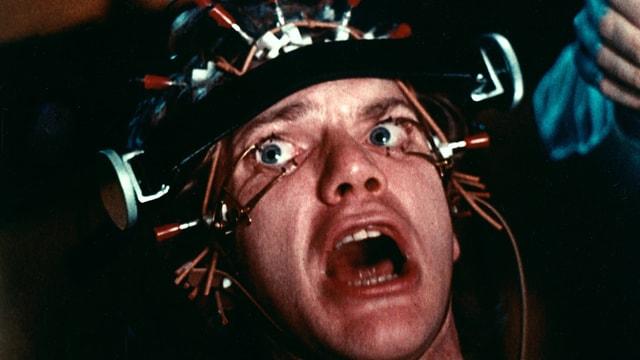 Ein Mann mit gequältem Blick mit einer Apparatur auf dem Kopf, die ihm die Augen offen hält.