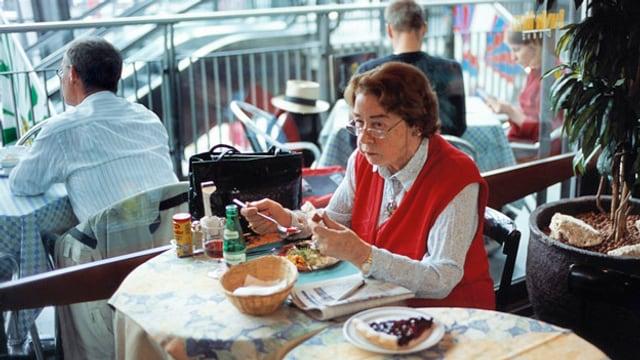 Eine Frau sitzt an einem Tisch und isst einen Salat.