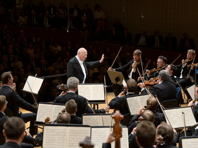 Das Bild zeigt einen Ausschnitt des Orchesters und den Dirigenten; es ist vom hinteren Teil der Bühne aus aufgenommen. Die Blickrichtung ist leicht erhöht. Wir sehen die vorderen Pulte der Streicher; den Dirigenten, und im Hintergrund das Publikum. Fast alle Musikerinnen und Musiker schauen zum Dirigenten. Er steht aufrecht da und blickt auf seine Partitur. Seinen linken Arm hebt er in die Richtung der ersten Geigen hoch, die Hand ist ebenfalls erhoben – als wolle er den Klang in der Schwebe halten. Die Bögen der Musikerinnen und Musiker sind in der Luft - gerade ist hier ein Ton zu Ende gegangen.