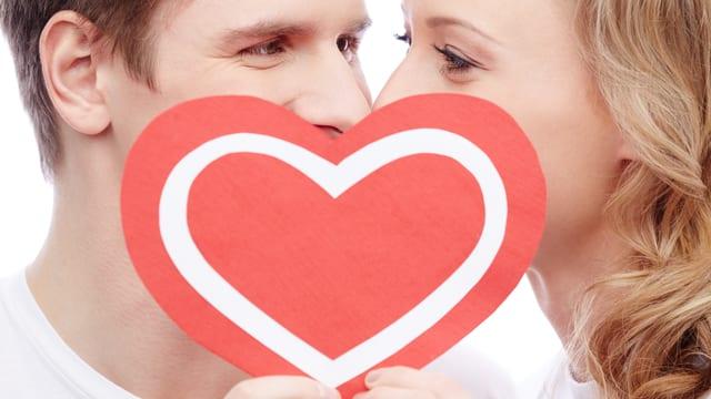 Ein Paar küsst sich hinter einem vorgehaltenen roten Herz.