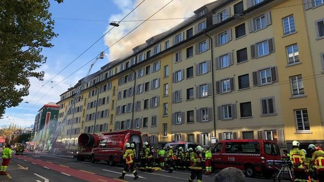 Feuerwehrautos und Feuerwehrleute in Arbeitskleidung vor einer Häuserzeile mit Rauch im Dachstock.