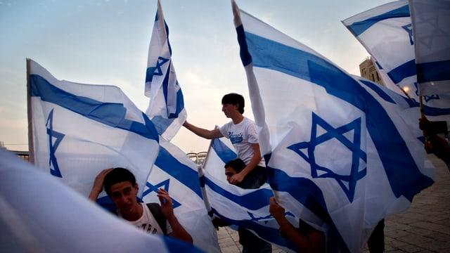 Ein paar junge Männer schwingen Israel-Fahnen.