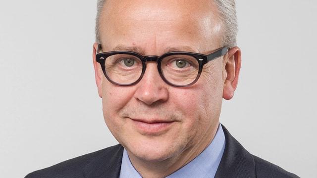 Ein Mann mit grauen Haaren und schwarzer Brille lächelt in die Kamera.