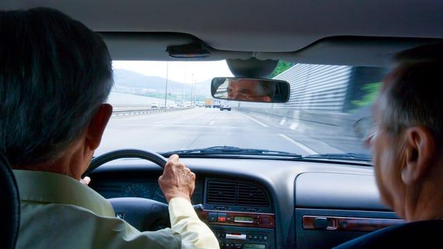 Zwei ältere Männer sitzen im Auto und fahren auf der Autobahn.