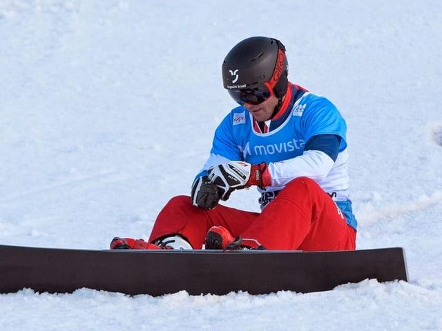 Nevin Galmarini che sesa cun ses snowboard en la naiv.
