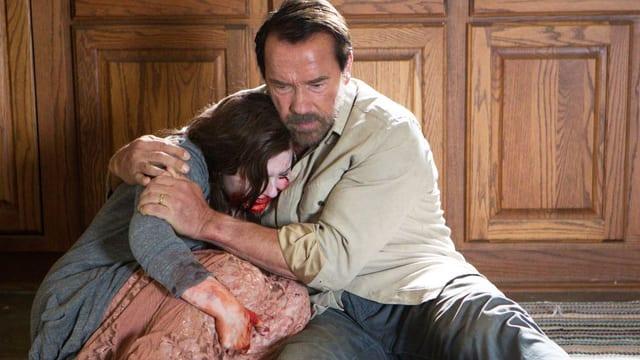 Ein Mann hält ein Mädchen, das Blut im Gesicht hat.