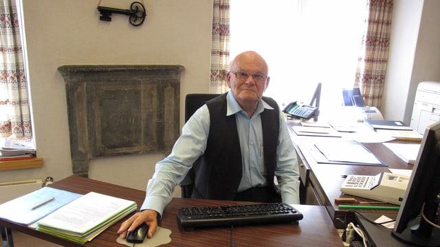 Ein Mann am Pult mit der Hand an der Computermaus.