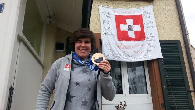 Sandra Thalmann mit Medaille vor ihrem Haus. Im Hintergrund ein Banner.