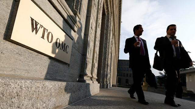 Zwei Personen vor dem WTO-Gebäude in Genf, ein WTO-Schild an der Wand.