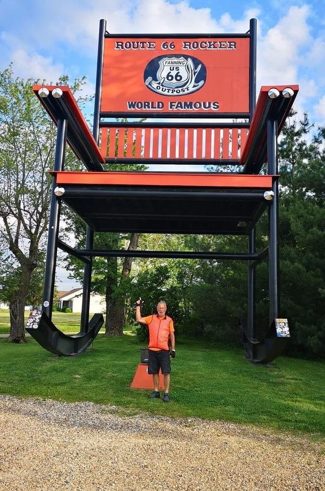 """Ein Mann vor einem Schild mit der Aufschrift """"Route 66 Rocker"""""""