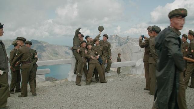 Jugendliche in Militär-Uniform posieren lächelnd vor einem Bergsee