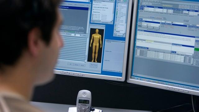 Telefonist am Computer. Auf Bildschirm ist Skizze des menschlichen Körpers zu sehen.