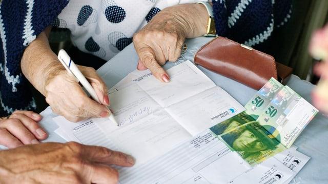 Ein Tisch mit Bankunterlagen und zwei 50er-Noten, die Hände einer alten Dame, die ein Formular unterzeichet.