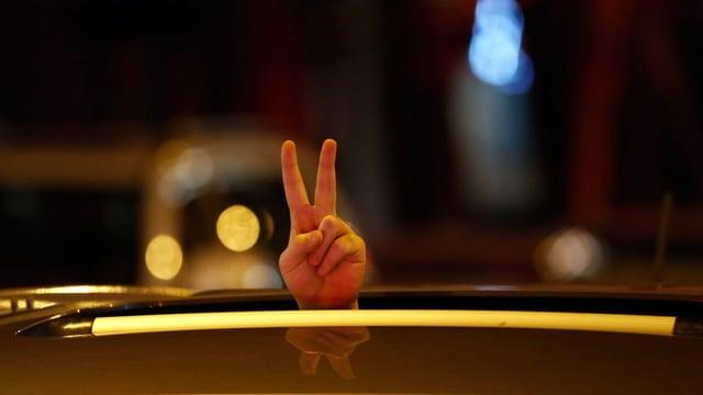 Mann in Teheran macht nach historischer Einigung im Atomabkommen ein Victory-Zeichen durch das Dach seines Autos. (Archiv)