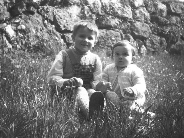 zwei Kinder sitzen auf Wiese