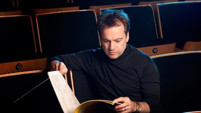 Ein Dirigent sitzt im Zuschauerraum eines Konzertsaals und schaut in ein Notenheft.