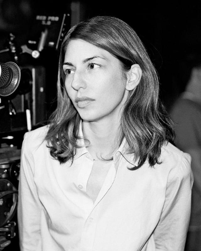 Die Regisseurin Sofia Coppola in weisser Bluse neben einer Kamera.