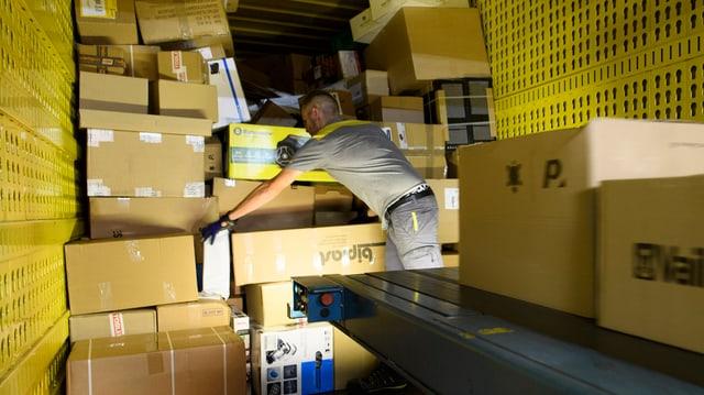 In lavurer da La Posta a Daillens (VD) stgargia pachets ord in container.