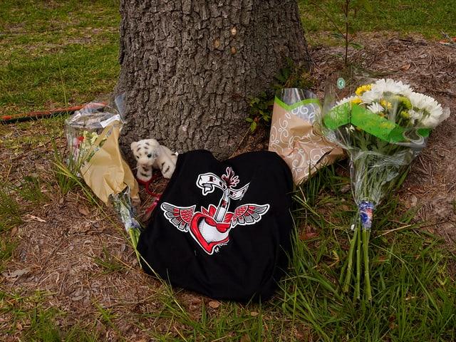 Blumen, Plüschtiere und T-Shirt am Fusse eines Baums liegend