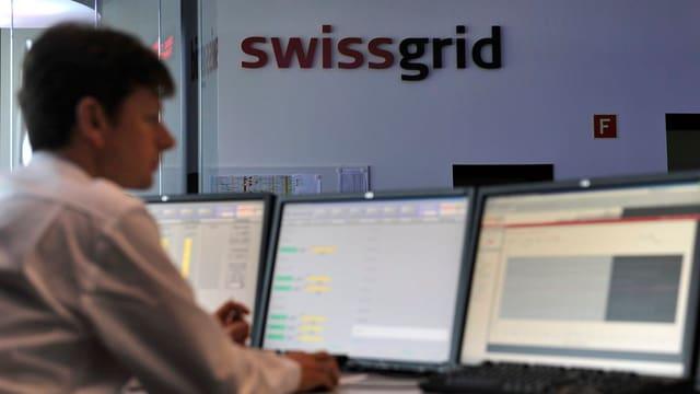 Mitarbeiter am Computer, im Hintergrund Firmenlogo von Swissgrid