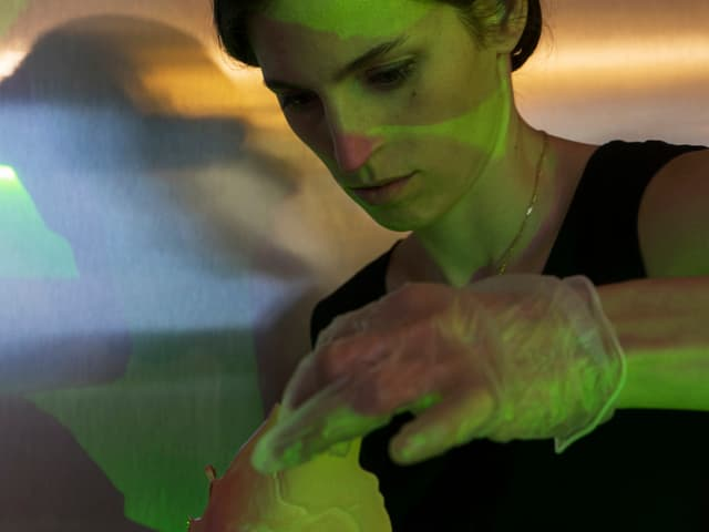 Eine Frau wird von verschiedenen Lichtern beleuchtet. Mit einem Gummihandschug hält sie ein undefinierbares Objekt in der Hand.