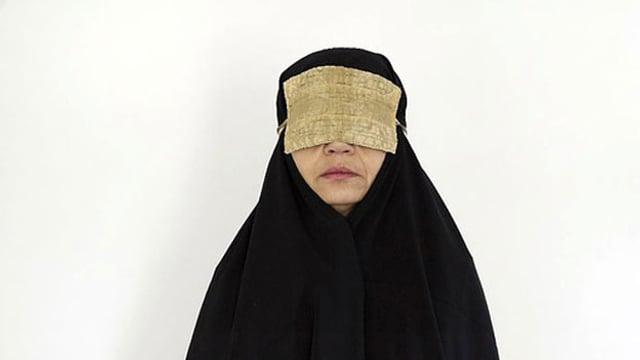 Eine schwarz verhüllte Frau mit einer Augenbinde.