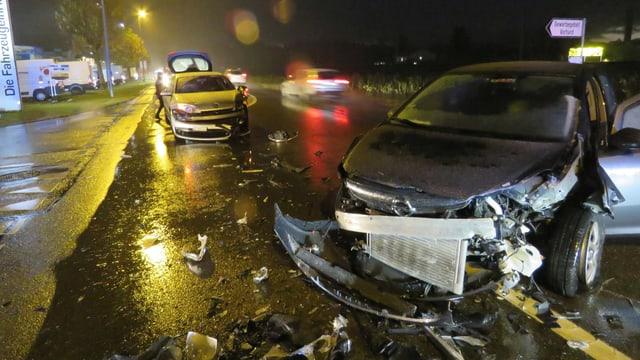 Zwei zerstörte Autos auf einer Strasse.