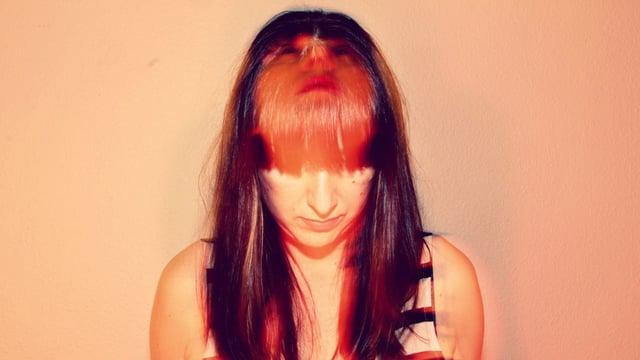 Eine Frau schaut nach unten. Durch eine Doppelbelichtung des Fotos sieht es so aus, als ob sie gleichzeitig nach oben schauen würde.