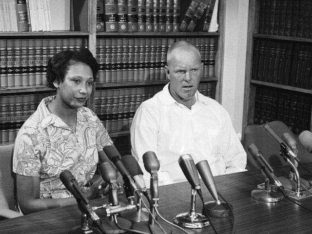 Schwarze Frau und weisser Mann sitzen vor vielen Mikrofonen.