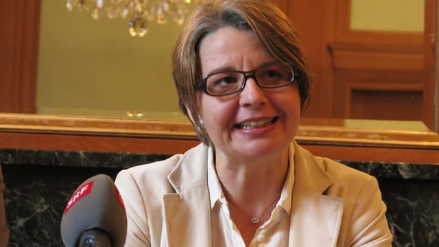 Kandidatin Martina Bernasconi sitzt an einem Pult und spricht zu Journalisten