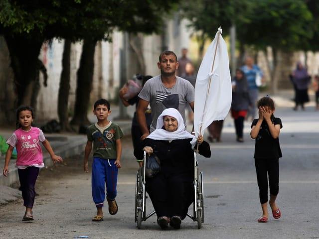 Frau in Rollstuhl mit weisser Flagge