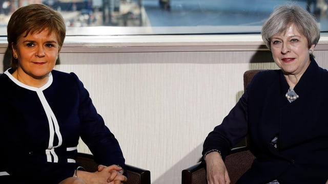 Nicola Sturgeon (l.) und Theresa May sitzen nebeneinander.
