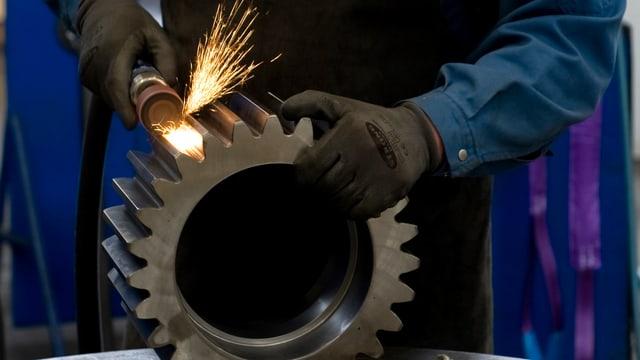 Ein Arbeiter schleift ein grosse Metal-Zahnrad, Funken stieben.