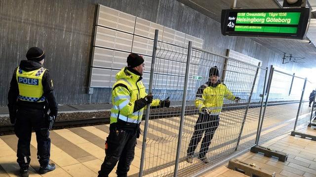 Polizistien stellen Gitter auf an einem Bahnhof.