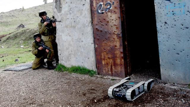 Ein Militärroboter sucht das Gelände ab, auf den Golanhöhen, im Hintergrund zwei israelische Soldaten.