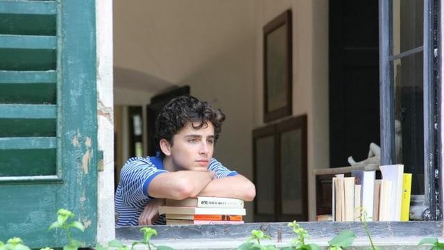 Ein Junge sitzt gelangweilt an einem Fenster.