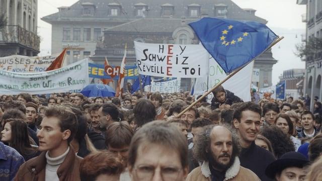 Menschen demonstrieren mit Fahnen und Plakaten während einem Marsch in der Stadt.