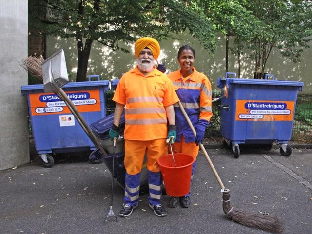 Ein Mann mit orangem Turban steht neben einer Frau. Sie haben Strassenputzsachen dabei.