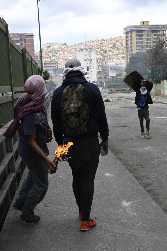 Zwei vermummte von hinten, einer wirft gerade einen brennenden Molotowcocktail. im Hintergrund Szenen einer Strassenschlacht.